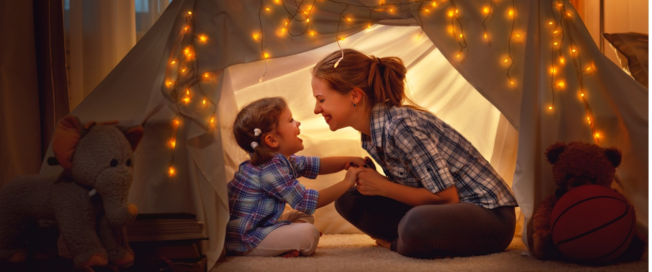 Happy mother and daughter playing in tent at home