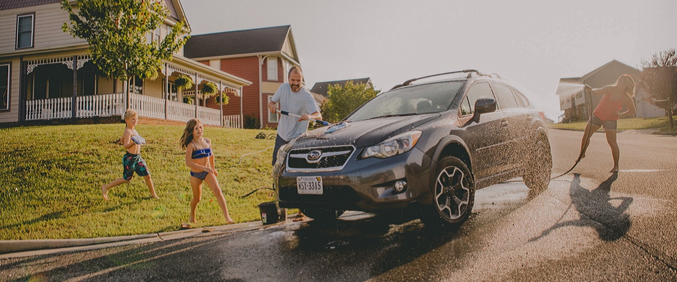 Family having fun washing car